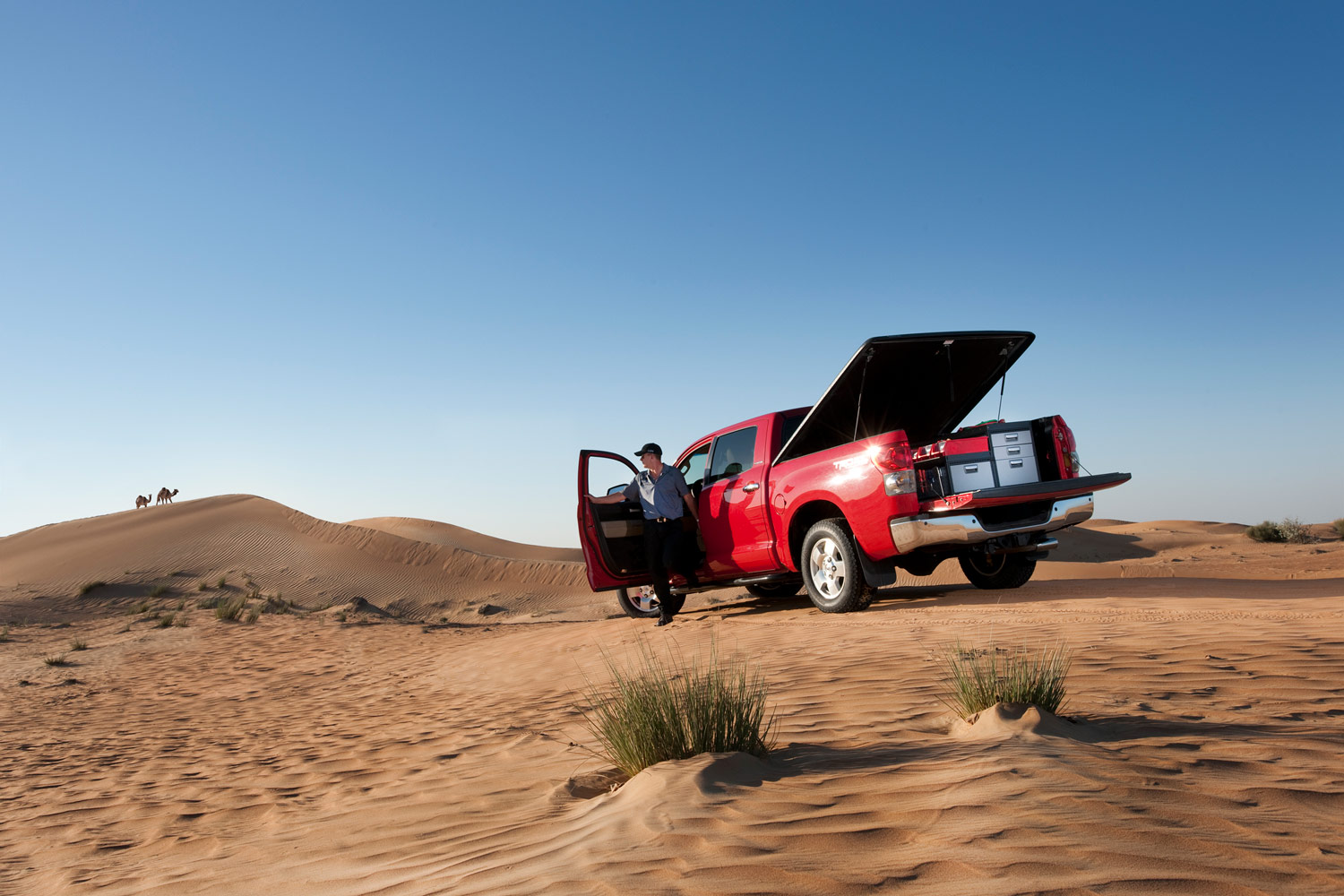 Worker's red pickup truck with modul-system racking in a desert